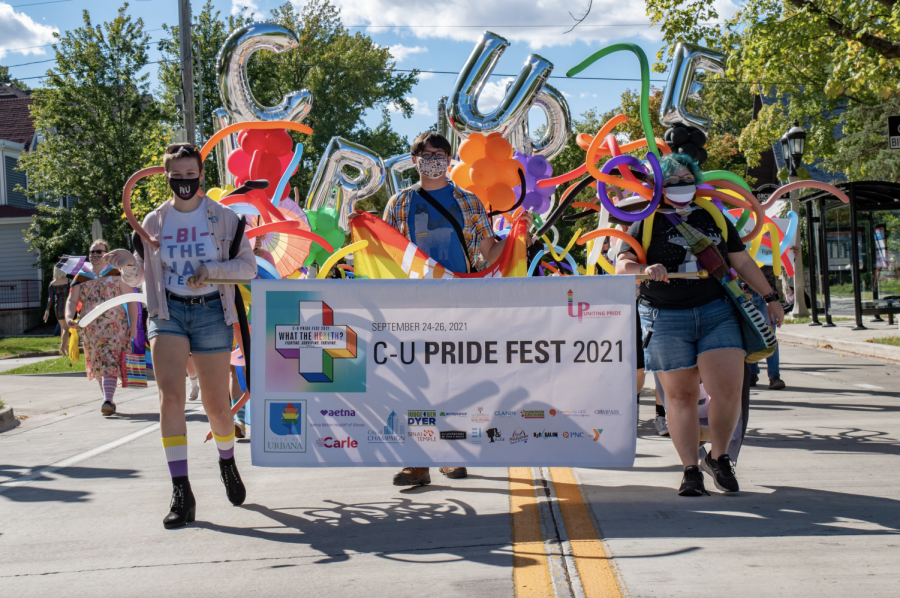 A group of people hold up a banner folowed by others with baloons at the start of the C-U Pride Parade on Saturday in Urbana.