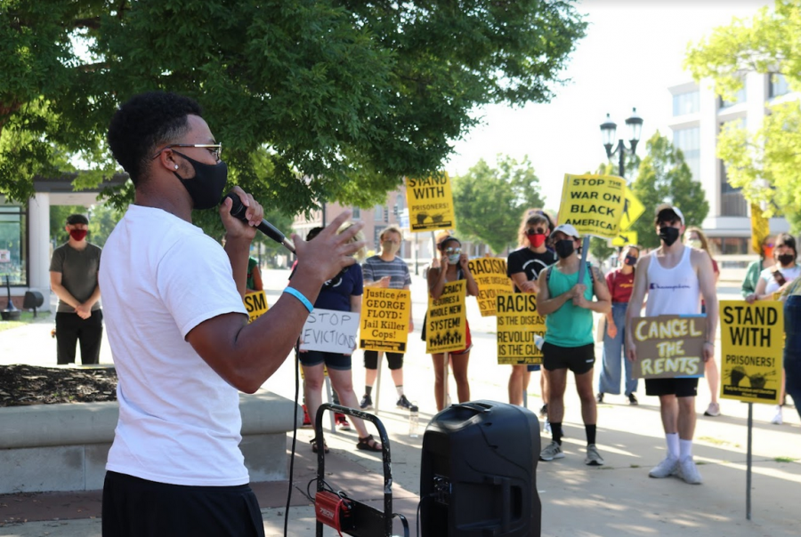 A protestor speaks in front of a group of people standing in solidarity against racism at the Black August protest on Aug. 28 outside the Sheriffs office in Champaign. The Party for Socialism and Liberation have been protesting the removal of the eviction moratorium.