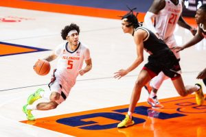 Andre Curbelo dribbles toward the basket during the game against Nebraska Feb. 25. There are three crucial  questions that the Illinois basketball team has yet to answer as they go into their first preseason game on Saturday.