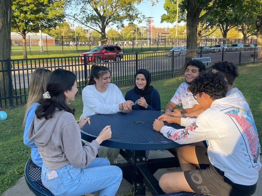 Students part of the MENA proposal sit around talking at a picnic bench on Oct. 12. Students work towards establishing a cultural house on campus for Middle Eastern North African cultures.