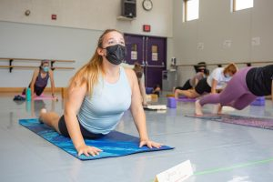 A student performs a cobra pose during the Yoga Practicum class on Monday morning. Yoga practice raises concerns for cultural appropriation.