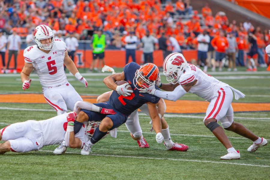 Running back Chase Brown gets tackled during the game against Wisconsin Oct. 9. Illini football receives an assessment on how theyve been performing at the past seven games.