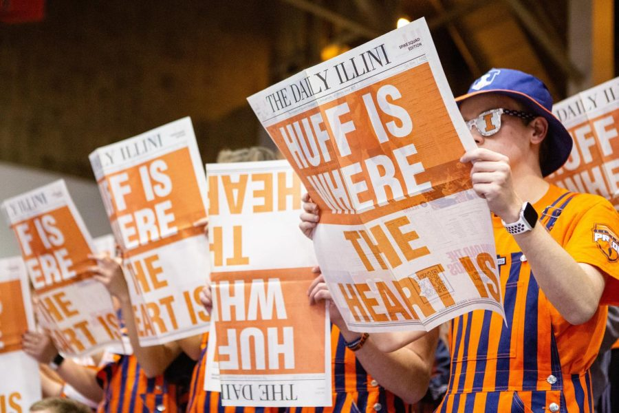 Illinois volleyball fans hold up copies of the Daily Illini during the game against Penn State on Nov. 15, 2019. After a long absence due to COVID-19, many fans have returned to watch Illinois home volleyball games.