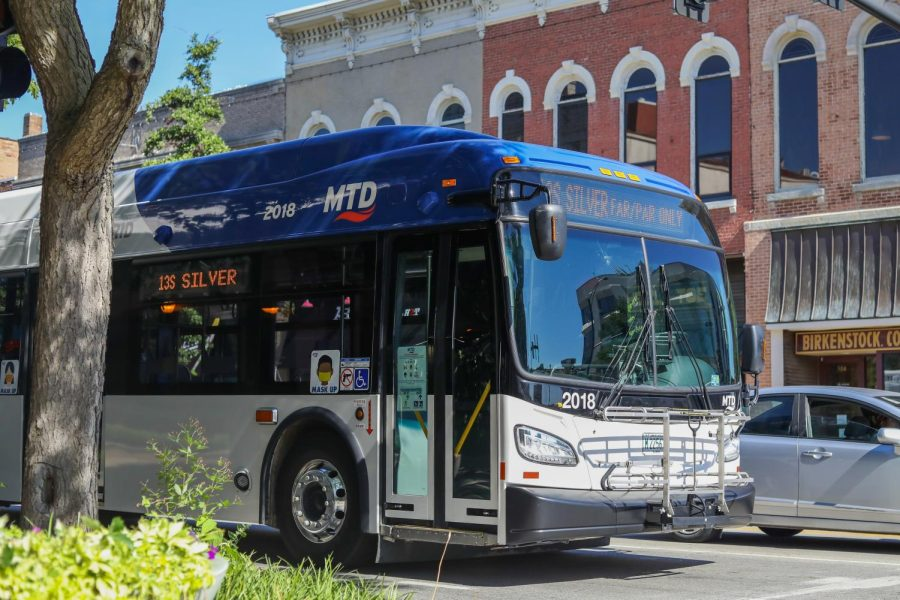 An MTD bus drives down a street for line 13 Silver. The MTD is short staffed creating service reductions.