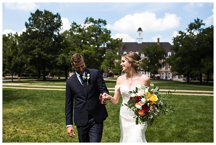 A couple who just married at UIUC walks across the Quad in their wedding attire.