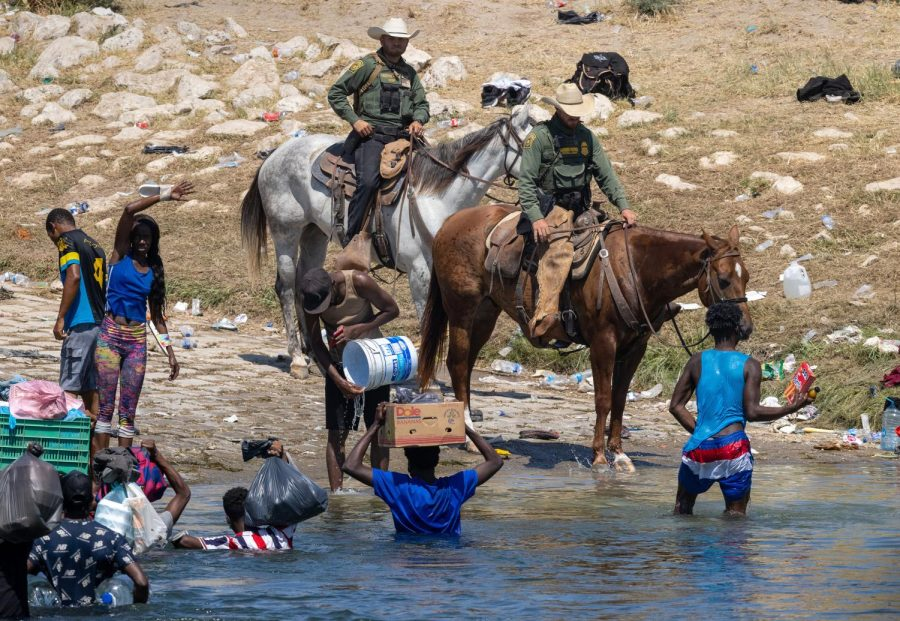 U.S. Border Patrol agents interact with Haitian immigrants on the bank of the Rio Grande in Del Rio, Texas on Sept. 20, as seen from Ciudad Acuna, Mexico. Columnist Eddie Ryan believes that it isnt possible for Haitians to seek asylum from America because of the current administration.