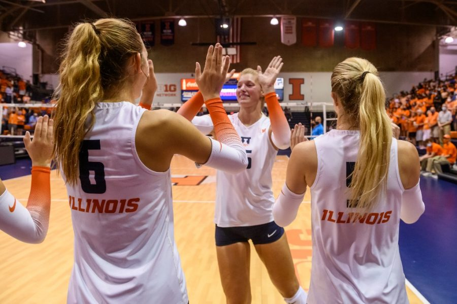 Graduate student Megan Cooney (15) high-fives teammates ahead of the teams match against Colorado at Huff Hall on Sept. 4. The Illini took down the No. 4 Purdue Boilermakers, 3-2, on Friday night.